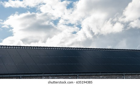 Newly build houses with solar panels attached on the roof against a sunny sky Close up of new building with black solar panels.Zonnepanelen Solar  panel, Zonne energie, Sun Energy