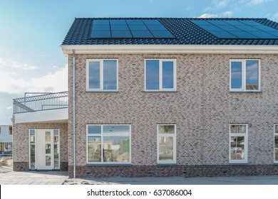 Newly build houses with solar panels attached on the roof against a sunny sky Close up of new building with black solar panels., Zonnepanelen Translation: Solar  panel, Sun energy