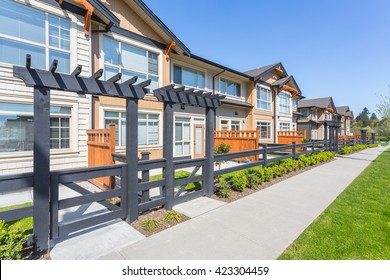 Newly built apartment buildings in the residential area with nicely trimmed lawn on a sunny day.