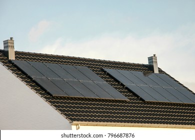 Newly built houses in the Netherlands with solar panels attached on the roof against a sunny sky Close up of new building  black solar panels.Zonnepanelen Translation: Solar  panel, Sun energy