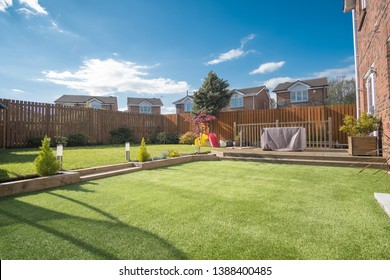 A newly completed and replanted landscaped garden with mixure of artificial and natural sown grass, borders planted, a new decking patio and garden ornaments surrounded by new erected wooden fencing.