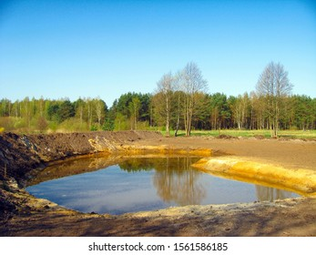 Newly dug pond on country field with sandy coasts.
