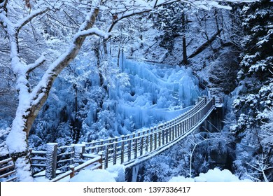 Newly fallen snow, a bridge, and large natural crystal clear ice pillars in Onouchi Hyakkei Valley, Chichibu, Saidama, Japan.