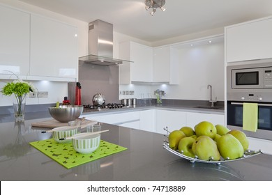 Newly fitted modern kitchen with built in appliances, utensils and basket of fruit