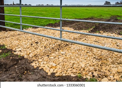 Newly laid hardcore rubble seen at the entrance to a farm field. The hardcore is used to give extra traction to farm vehicles entry the large, arable field.