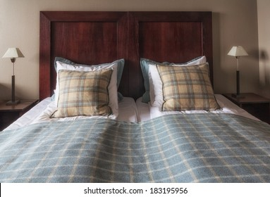 newly made hotel bed with checkered blanket