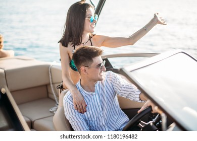 Newly married caucasian couple driving sailboat, enjoying water summer adventure, spending honeymoon in the sea cruise, romantic relationship, happy young family