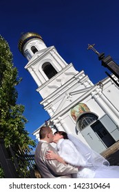 newly married couple before the church