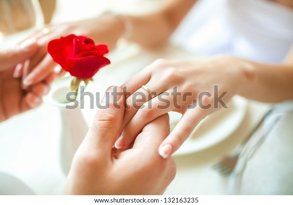Newly married couple holding hands with rings against wedding dress