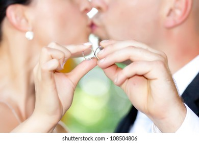 Newly married couple - kissing behind wedding rings