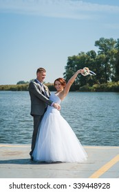 Newly married couple posing on the bank of the river