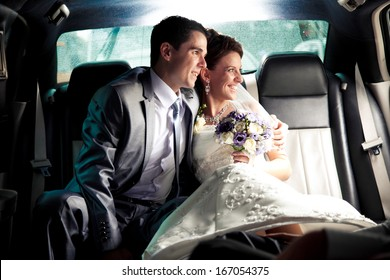 Newly married couple sitting on backseat of the car and looking out of window