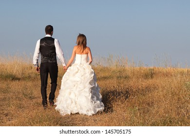 Newly married couple walking on their honeymoon for a desert landscape at sunset.