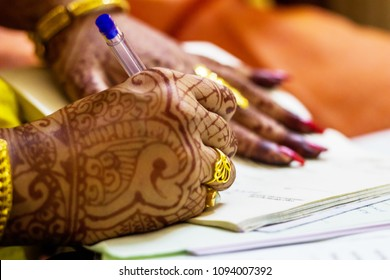 a newly married indian bengali wife with golden wedding ring signing marriage registration form