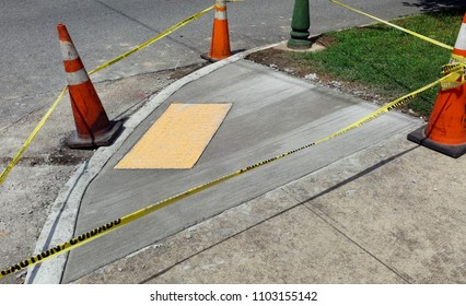 Newly poured cement handicapped ramp with no-slip pad, orange safety cones and caution tape.