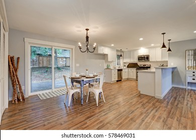 Newly remodeled one story craftsman home interior. Dining area positioned beside white kitchen boasts white washed dining table facing glass doors to the backyard. Northwest, USA
