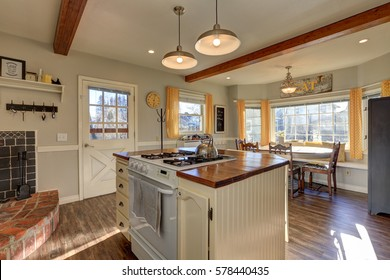 Newly renovated Kitchen boasts wood beams on ceiling, pale grey walls, white island with wood counter top and hardwood floor. Northwest, USA