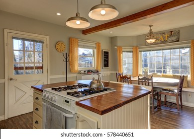 Newly renovated Kitchen and breakfast nook  boasts wood beams on ceiling, pale grey walls, white island with wood counter top and hardwood floor. Northwest, USA