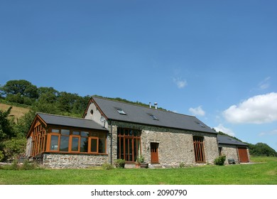 Newly restored stone barn with slate roof in rural countryside.
