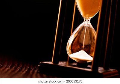 Newly turned hourglass with running sand measuring the passing time to a deadline or expiry of a fixed time period, close up on a dark background