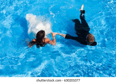Newly wed bride and groom with their bridal dress and suit lying in a swimming pool, unrecognizable shot from above.