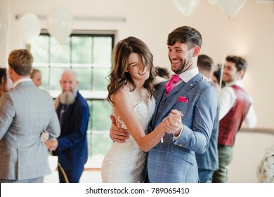 Newly wed couple are dancing together on their wedding day with all of their guests.