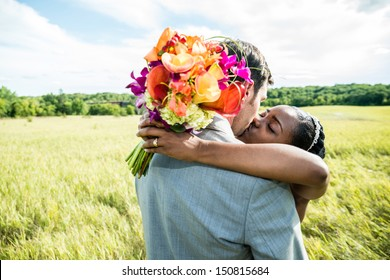 Newly wed couple kissing on a grass field