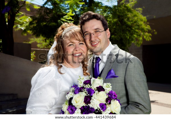 A newly wed couple snuggles close for a post wedding ceremony portrait.