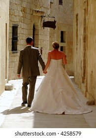 Newly wed couple walking in the old city streets in Malta