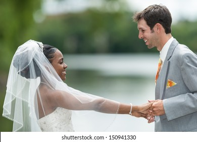 Newly wed interracial couple holding hands near a lake