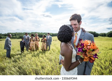 Newly wed interracial couple kissing with people watching in the background