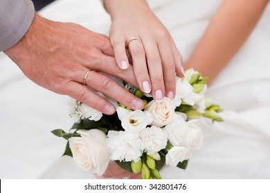A newly weding couple place their hands on a wedding bouquet showing off their wedding rings.