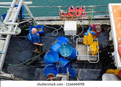 NEWLYN, ENGLAND - JUNE 20: Commercial fishermen clearing the deck for departure on a fishing boat in Newlyn harbour. In Newlyn, Cornwall, England. On 20th June 2018.
