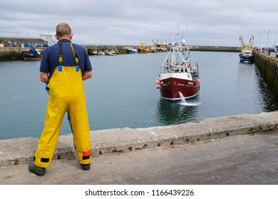 NEWLYN, ENGLAND - JUNE 20: Fisherman watches as a fishing boat returns from a fishing trip to sea, in Newlyn harbour. In Newlyn, Cornwall, England. On 20th June 2018.