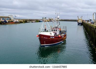 NEWLYN, ENGLAND - JUNE 20: Fishing trawler boat returning to Newlyn harbour. In Newlyn, Cornwall, England. On 20th June 2018.