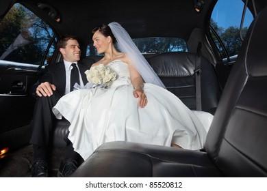 Newlywed bride and bridegroom in car