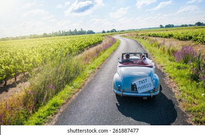 A newlywed couple is driving a convertible retro car on a country road for their honeymoon, top view