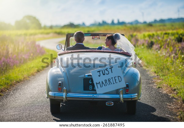 A newlywed couple is driving a convertible retro car on a country road for their honeymoon, rear view