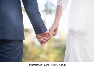 A newlywed couple holding hands