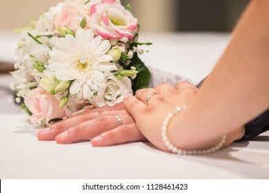 Newlywed couple holding hands and displaying wedding rings, wedding bouquet on altar in church