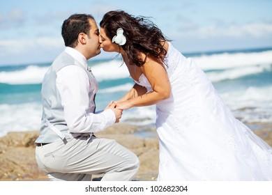 newlywed couple kissing on beach rocks