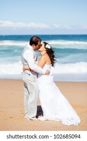 newlywed couple kissing on beach