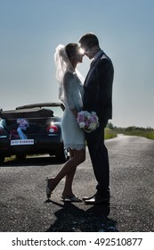 Newlywed couple looking at each other.  They are standing on a country road, the sun shines between their faces. a convertible car waiting for them, to go on honeymoon. Shot with flare