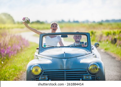 A newlywed couple on a lovely country road for their honeymoon. The bride is lifting her bouquet.