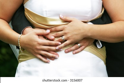 Newlywed couple showing off rings, groom's hands around the waist of bride