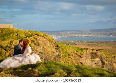 A newlywed couple sitting on a cliff overlooking a scenic view during a sunset.