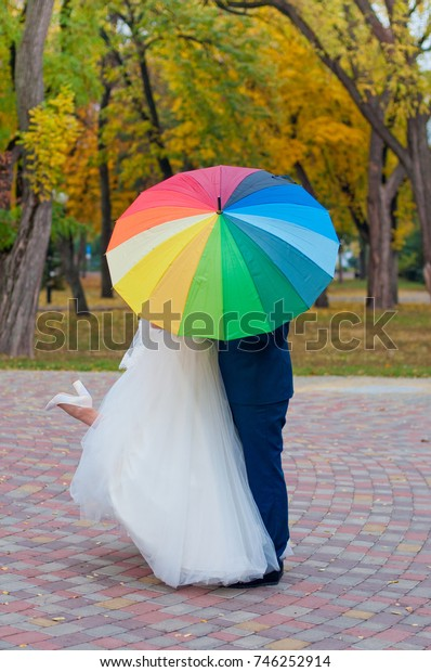 Newlywed couple staying under colorful umbrella in autumn park