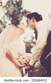 Newlywed couple tenderly kissing outdoors