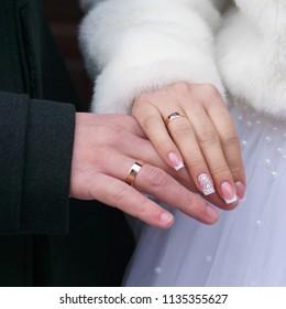 Newlywed couples hands with golden wedding rings close up.