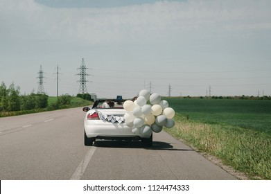 A newlywed wedding couple is driving a convertible retro car with balloons on a country straight road for their honeymoon. Way near spring field of flowers. The best day and marriage. Just married.